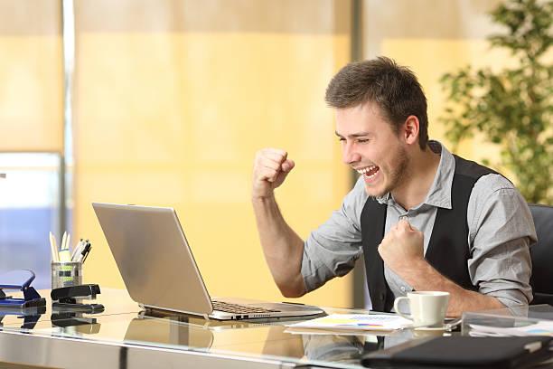 excited businessman online with laptop - die besten apps stock-fotos und bilder