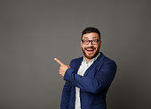 istock Excited businessman pointing up at copy space 1084031516