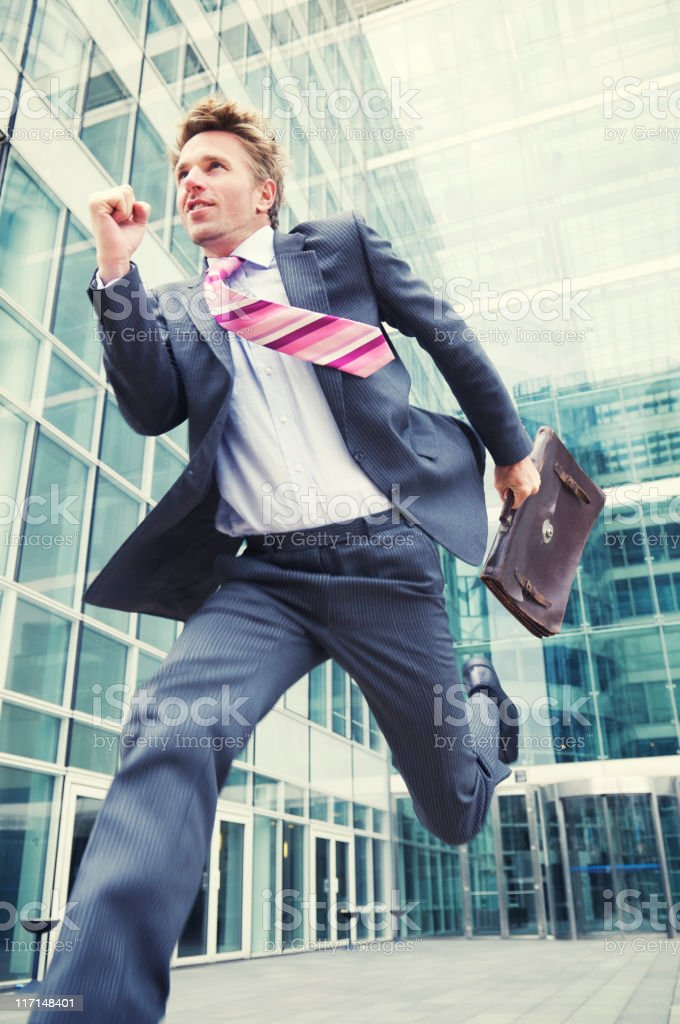 Excited Businessman Running Out of Office with Briefcase stock photo