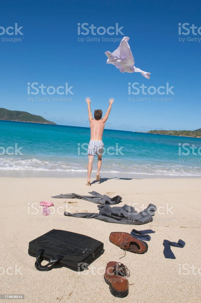 Excited Businessman Running Undressing on the Beach Feeling Free stock photo