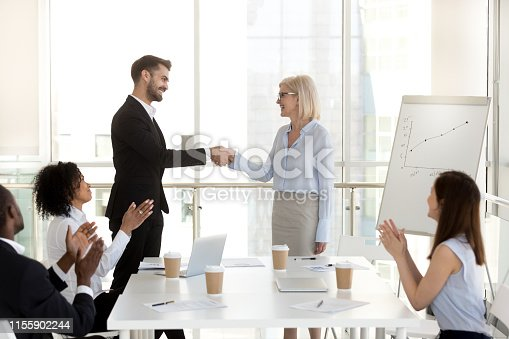 istock Excited businessman shaking hand of businesswoman at company meeting 1155902244