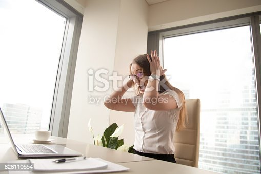 istock Excited businesswoman celebrating win screaming of joy looking at laptop 828110554