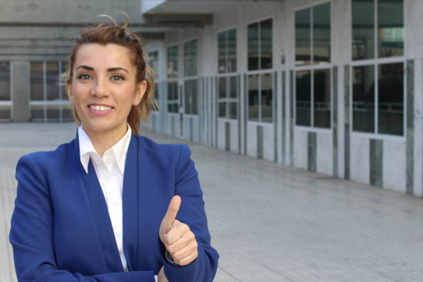 Excited businesswoman giving a thumbs up Excited businesswoman giving a thumbs up. cheesy grin stock pictures, royalty-free photos & images