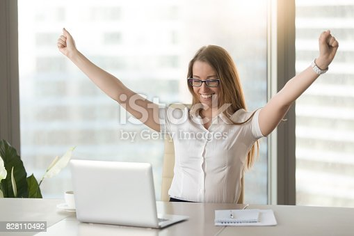 istock Excited businesswoman raising hands celebrating business success looking at laptop 828110492