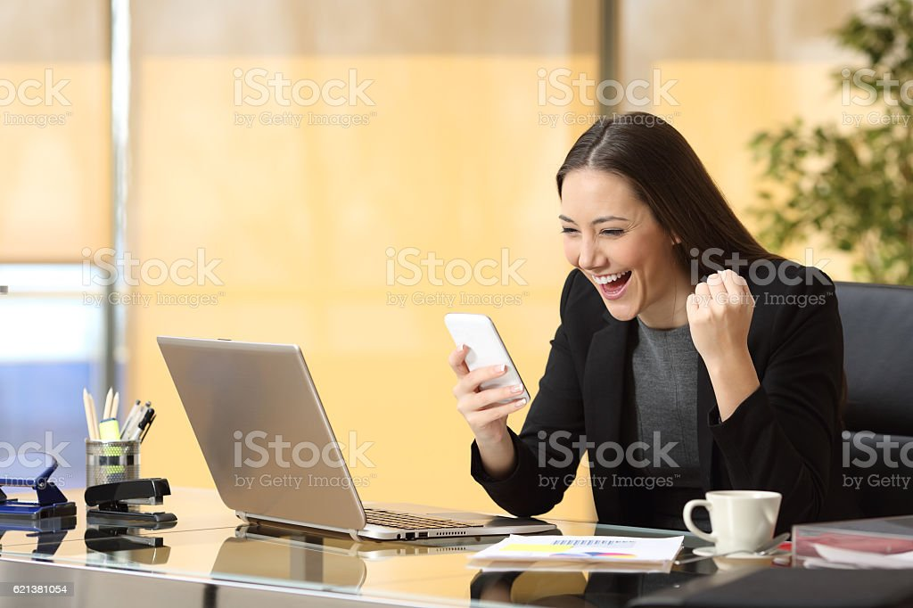 Excited businesswoman reading a smart phone stock photo
