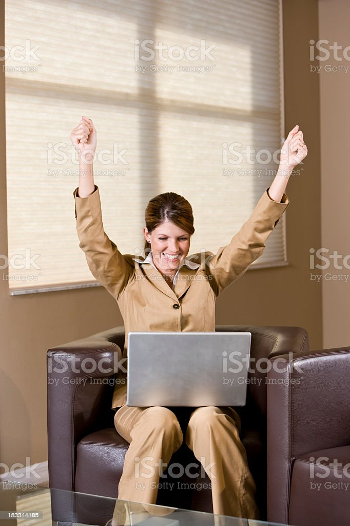 Excited businesswoman sitting armchair looking at laptop with ra stock photo