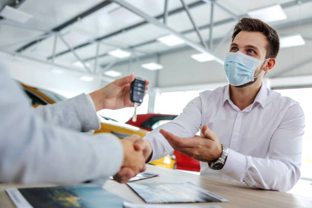 Excited car buyer with face mask shaking hands with car seller and taking car keys while sitting in car salon. stock photo