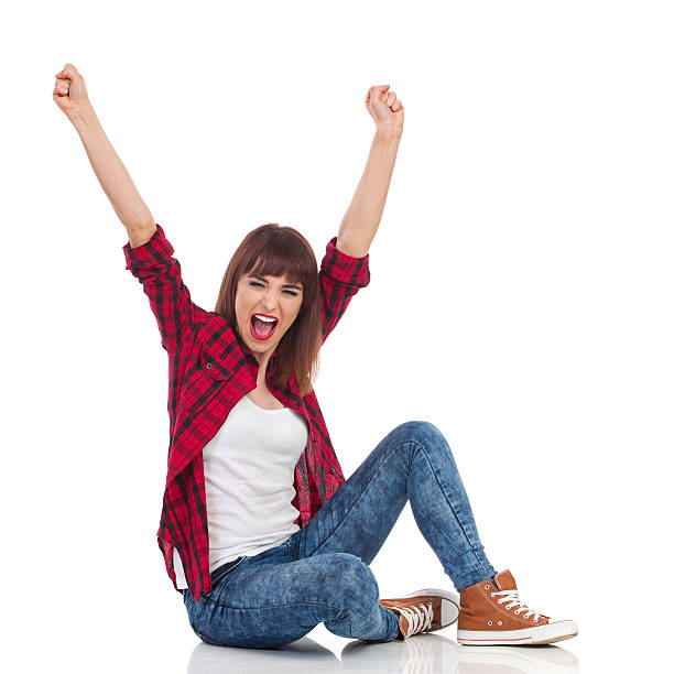excited casual woman cheering - sitting on floor stock photos and pictures
