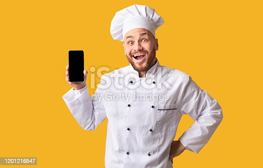 istock Excited Chef Showing Mobile Phone Empty Screen On Yellow Background 1201216547