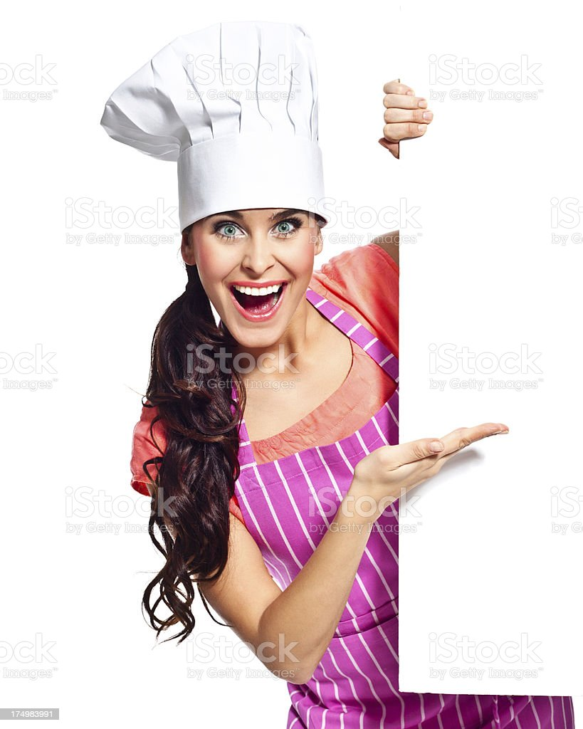 Excited chef with whiteboard Portrait of happy young woman wearing chef's hat pointing at the whiteboard and laughing at the camera. 20-24 Years Stock Photo