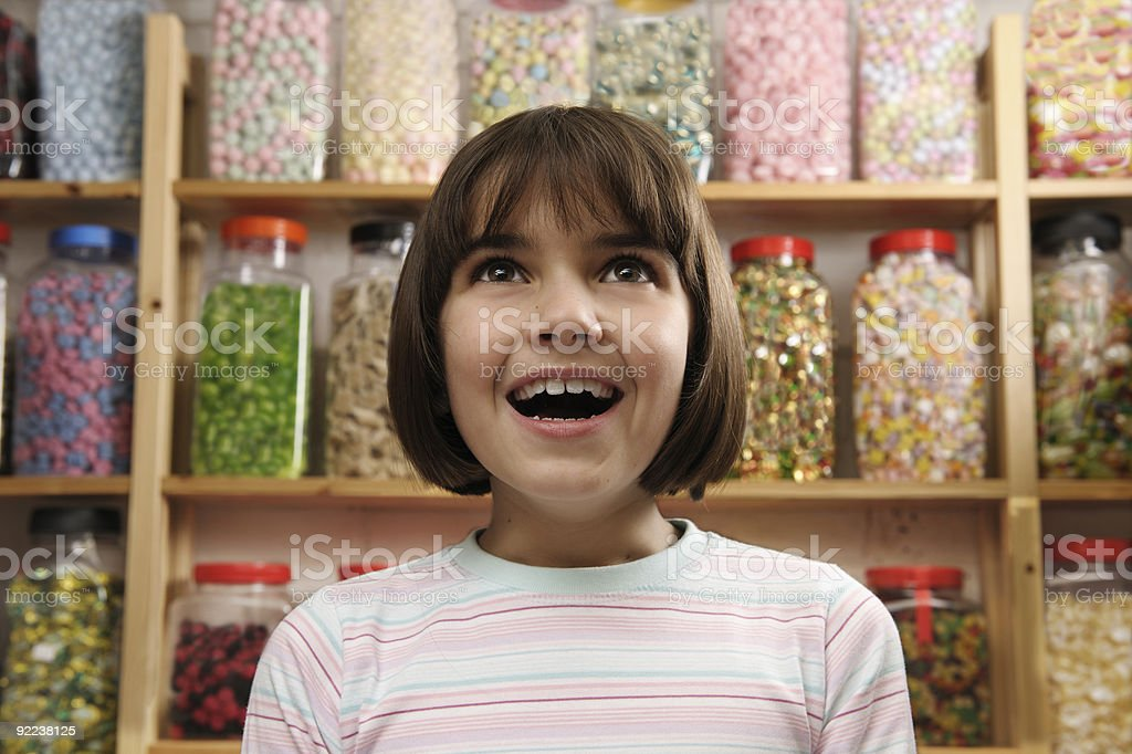 Excited child in a candy store stock photo