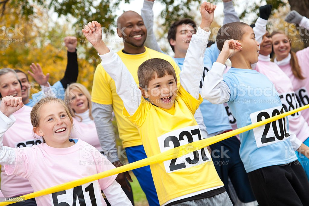 Excited children and adults happily crossing a race finish line stock photo