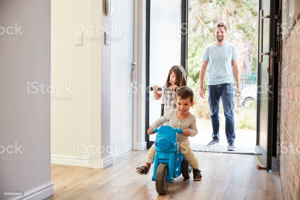 Excited Children Arriving Home With Father stock photo