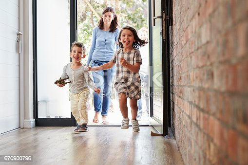670900812 istock photo Excited Children Arriving Home With Parents 670900796