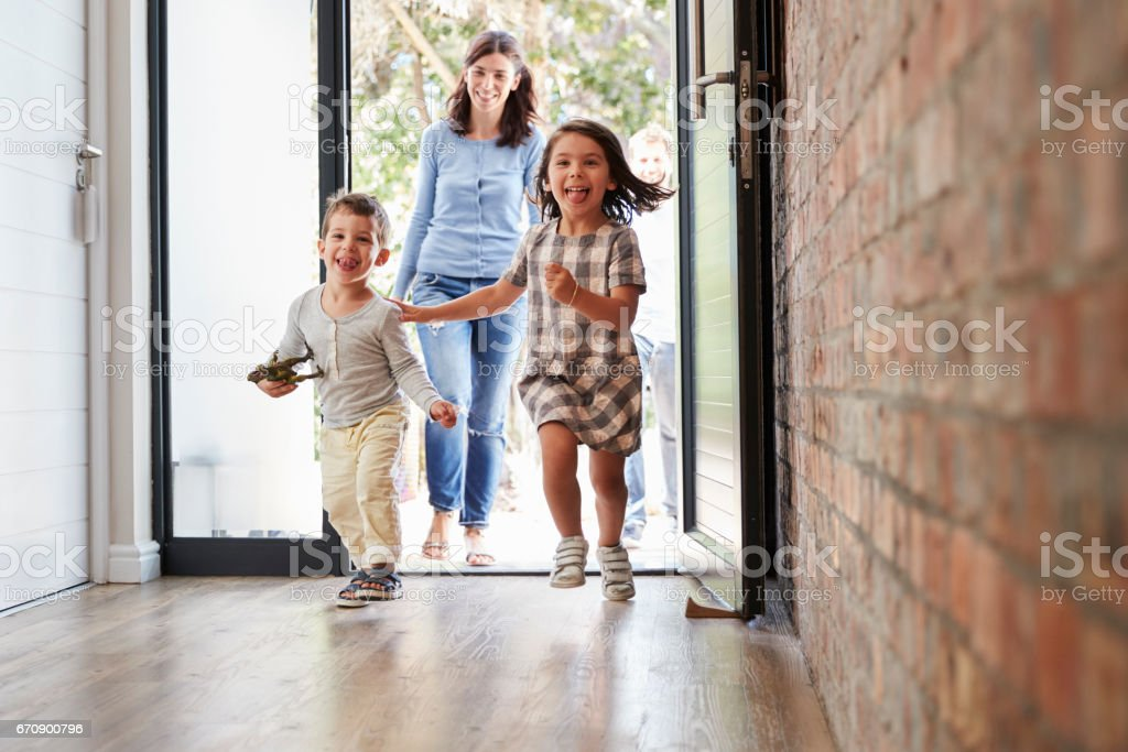 Excited Children Arriving Home With Parents stock photo