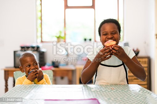 Excited children bite into cupcakes