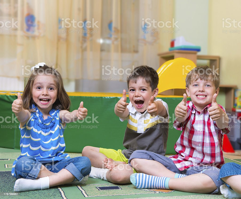 Excited children holding thumbs up stock photo