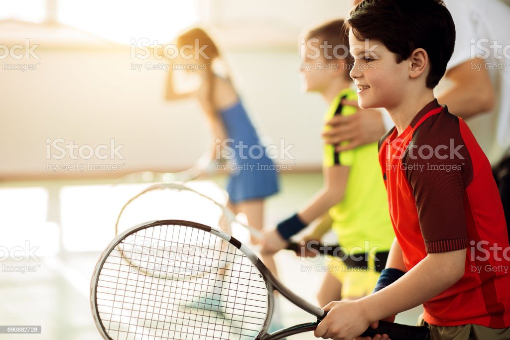 Excited children playing tennis on court stock photo