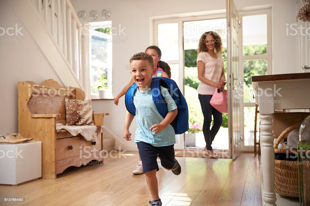 Excited Children Returning Home From School With Mother stock photo
