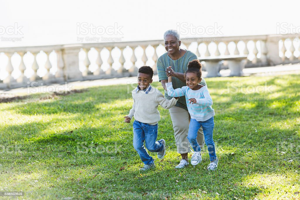 Excited children running with their grandmother stock photo