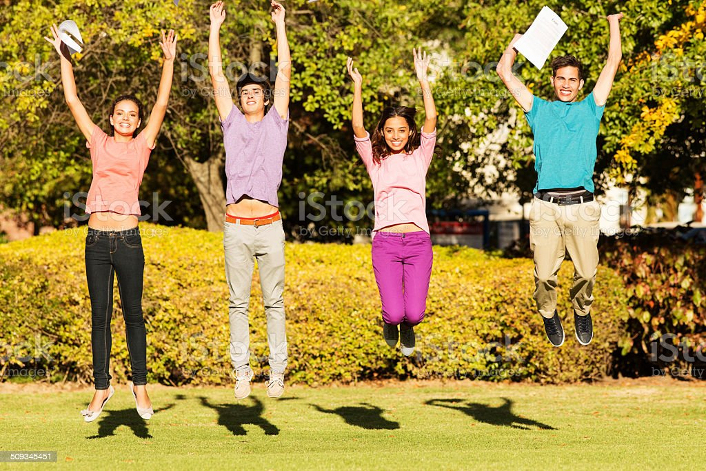 Excited College Students With Exam Results Jumping On Campus stock photo