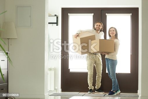938682826istockphoto Excited couple carrying boxes entering house moving into new home 951349658