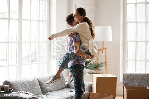 938682826istockphoto Excited couple celebrating moving day, man lifting embracing happy woman 938682824