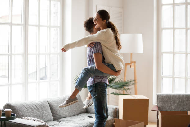 Excited couple celebrating moving day, man lifting embracing happy woman - foto stock