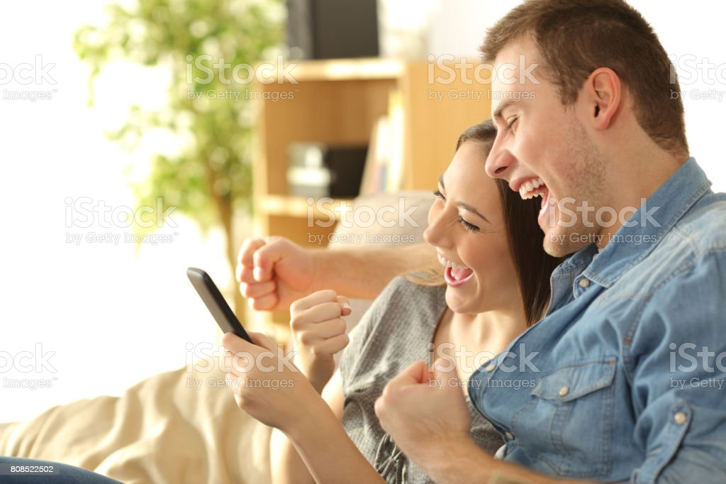 Excited couple checking content in a phone stock photo