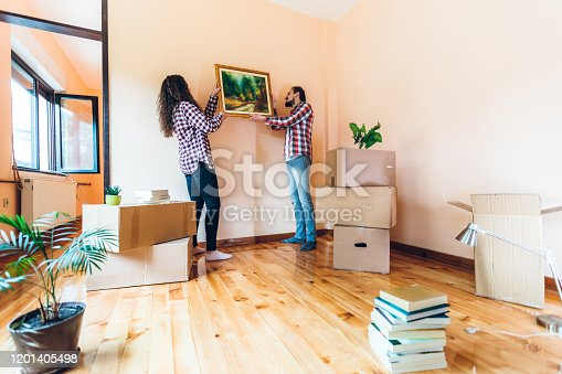 Excited cute Caucasian couple hanging picture on wall in her new apartment.
