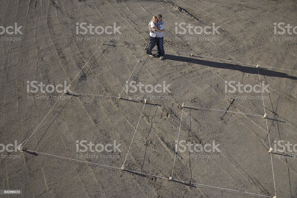 Excited couple hugging at construction site of new home royalty free stockfoto