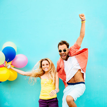 Happy couple with balloons jumping