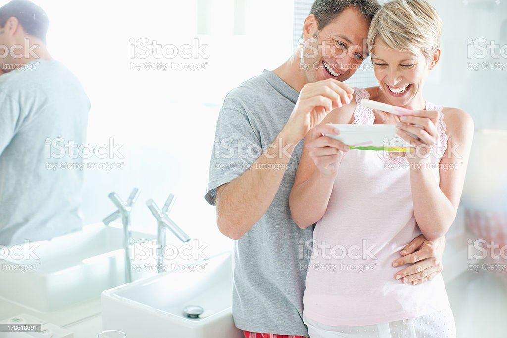 Excited couple looking at pregnancy test stock photo