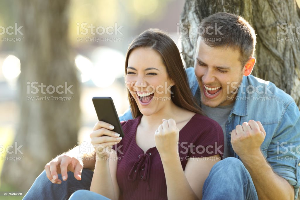 Casal animado ler notícias em um telefone - foto de acervo