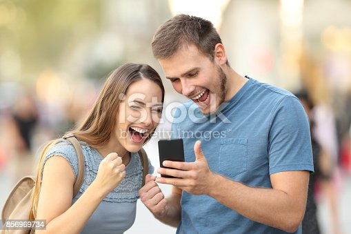 istock Excited couple receiving good news on line outside 856969734