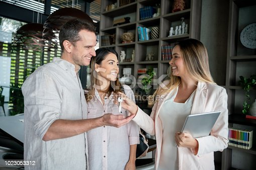 Excited couple receiving the keys from their real estate agent all looking very happy and smiling and agent holding a tablet