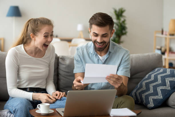 Excited couple screaming with joy reading good news in letter Excited amazed happy couple winners screaming with joy rejoicing reading good news holding mail paper letter celebrating taxes refund, cheap great offer, economy promotion in bank statement at home refund stock pictures, royalty-free photos & images