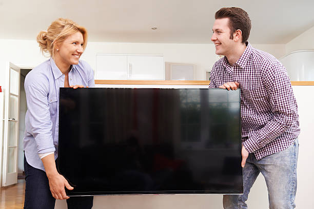 excited couple setting up new television at home - happy person buy appliances stock photos and pictures