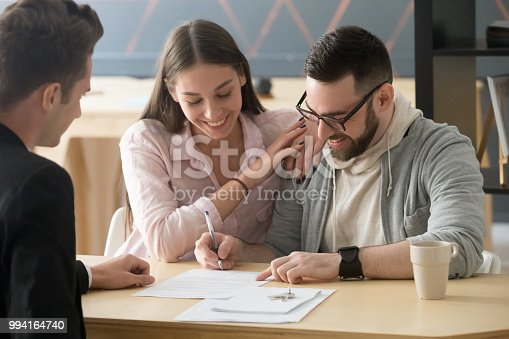 istock Excited couple sign purchase contract in realtor office 994164740