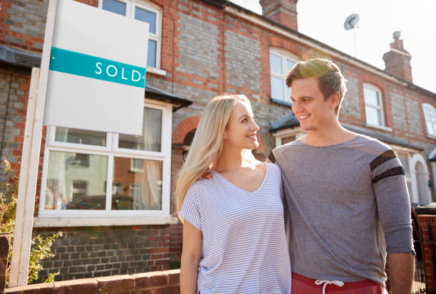 Excited Couple Standing Outside New Home With Sold Sign stock photo