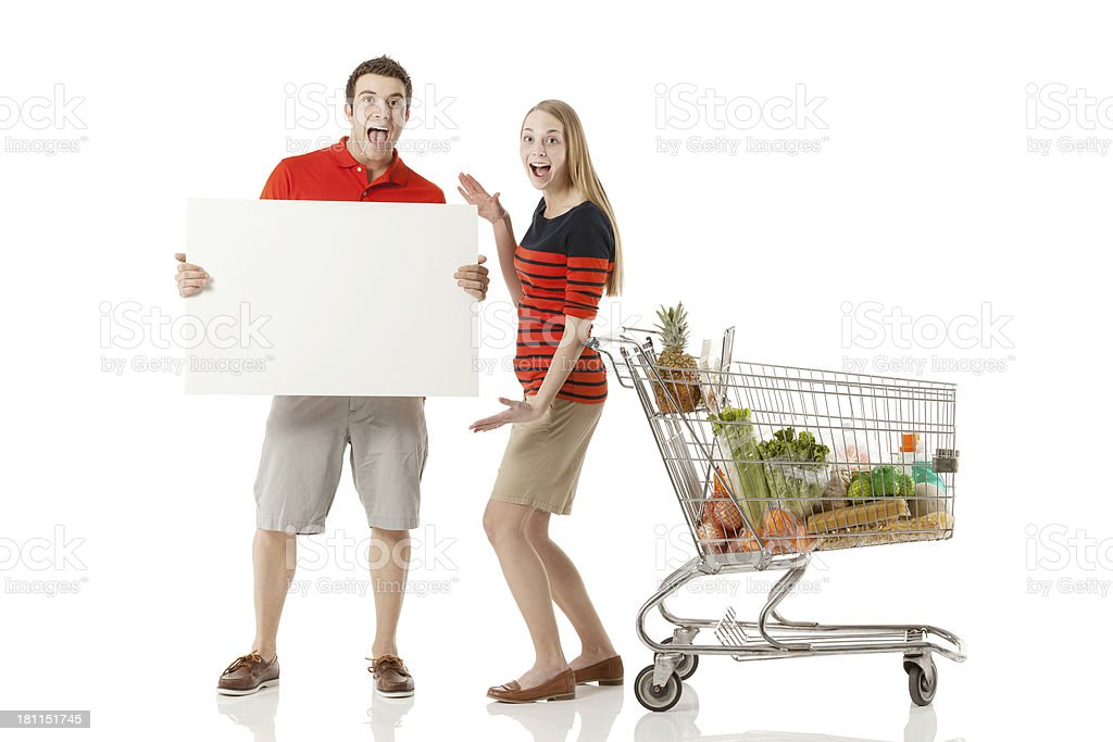 Excited couple with a placard in supermarket stock photo