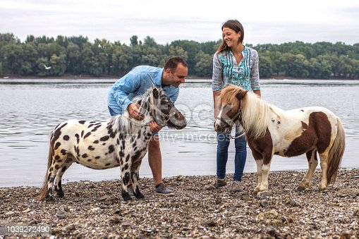 Excited couple with pony by river