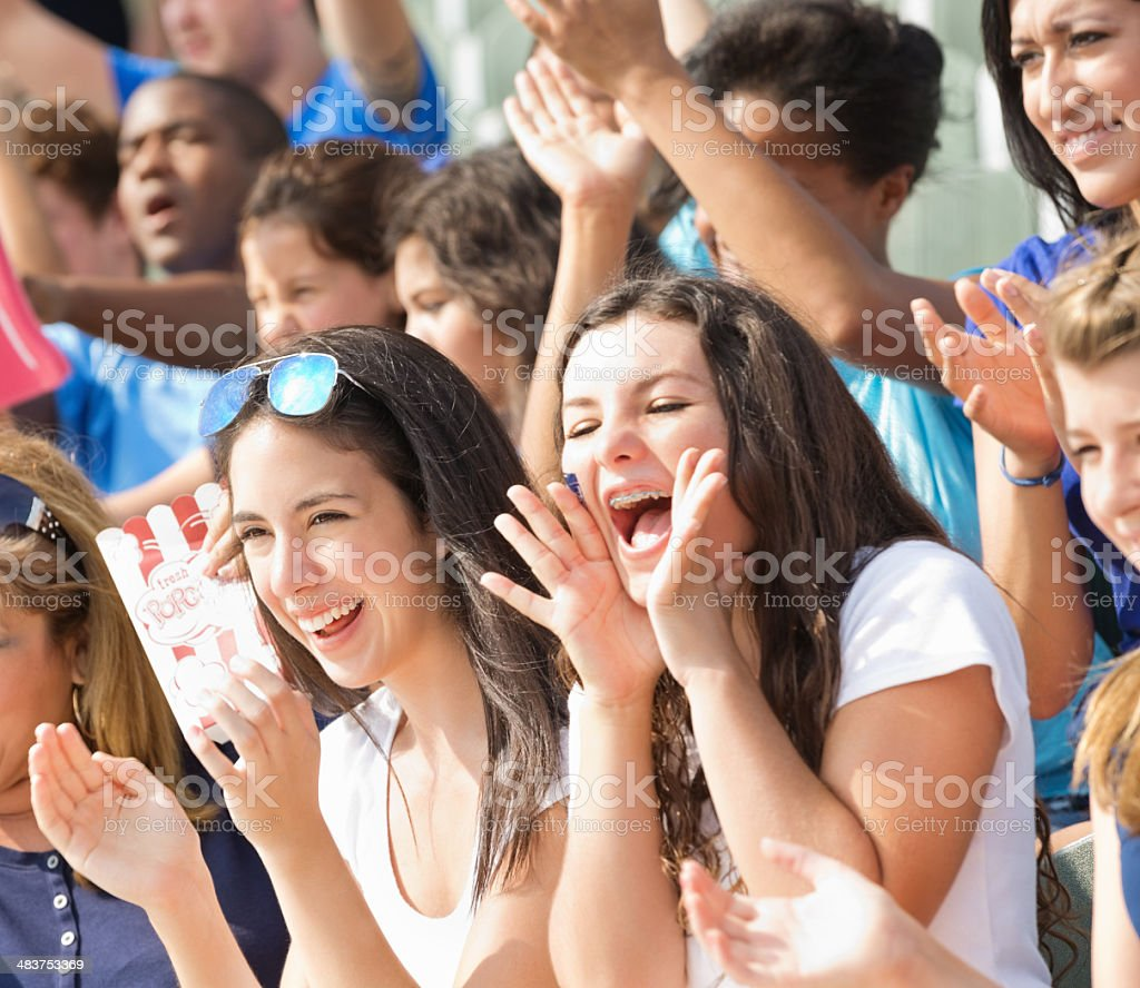 Excited crowd of fans cheering on team from stadium bleachers stock photo