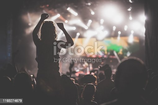 Rear view of large group of unrecognizable people having fun and enjoying at illuminated rock concert. One woman is being carried on shoulders with her hand in the air. Others are dancing, cheering and applauding.