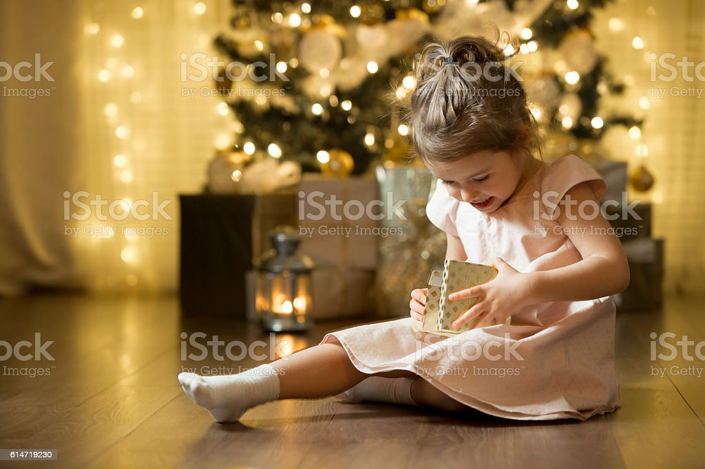 Excited curious little girl smiling, opening christmas gifts.​​​ foto