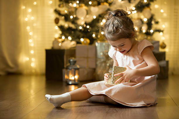 excited curious little girl smiling, opening christmas gifts. - christmas gift family bildbanksfoton och bilder