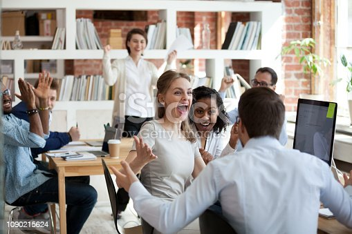 Excited diverse business team employees screaming celebrating good news business win corporate success, happy multi-ethnic colleagues workers group feeling motivated ecstatic about great achievement