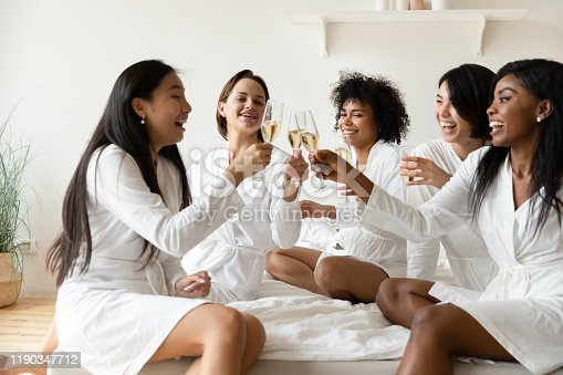 istock Excited diverse girls friends wear robes celebrating clinking champagne glasses 1190347712