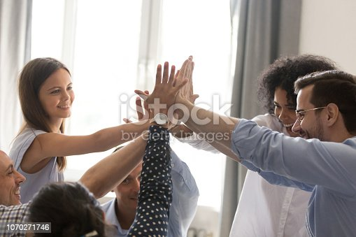 istock Excited diverse office team giving high five together celebrating success 1070271746