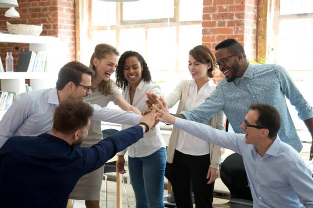 upphetsad olika arbetstagare varandras händer vid teambuilding aktivitet - högväxt bildbanksfoton och bilder